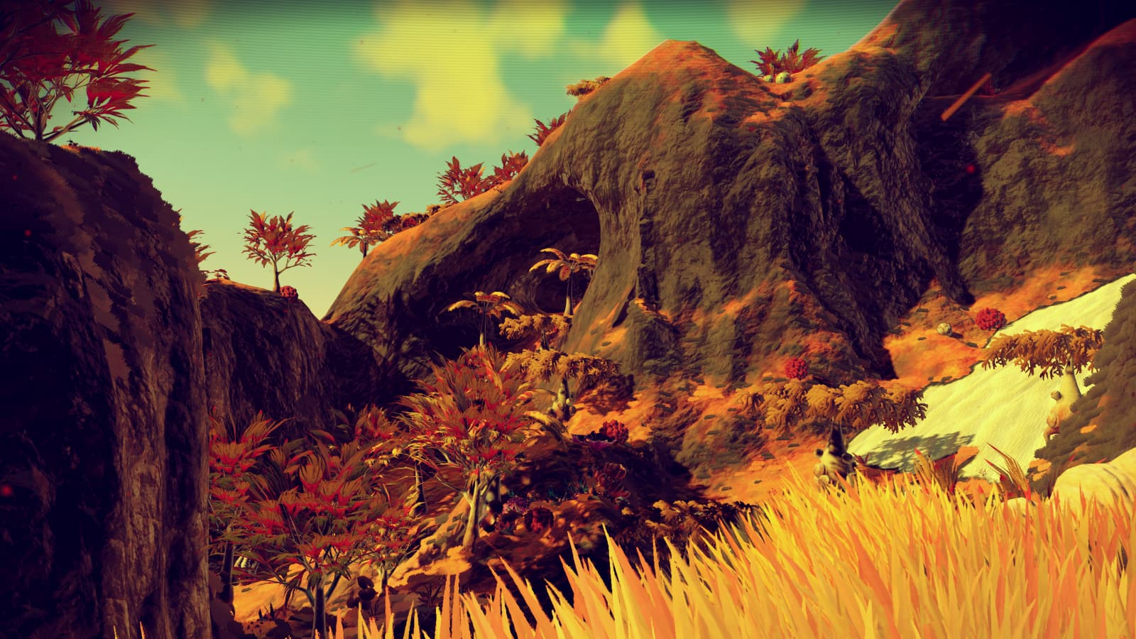 Photo of a craggy elevation on a golden lush world from No Man's Sky version 1.1
